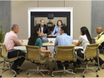 Four people at a table conducting a video conference with two people on a video screen